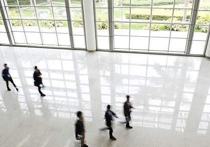 Office workers walking in front of large windows with a view of outdoor gardens.