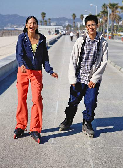 Teenage boy and girl on inline skates.