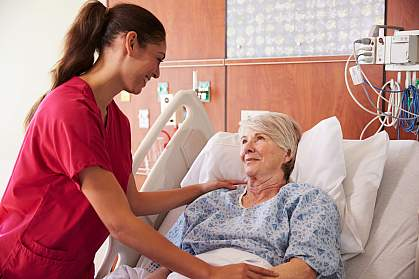 Nurse talking to an older woman in a hospital bed