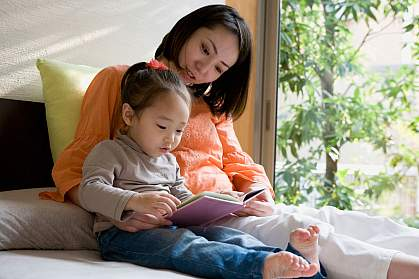 Mother and daughter reading a picture book.