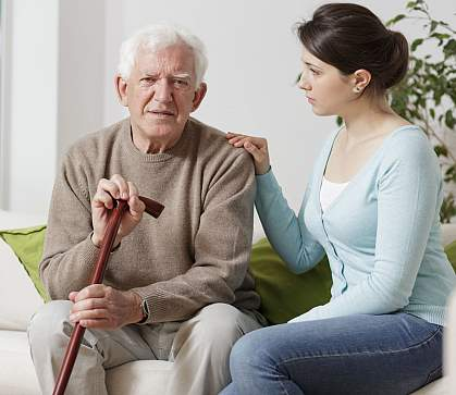 Elderly man with walking stick and caregiver