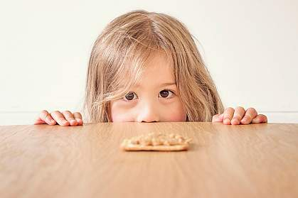 Young girl staring a peanut butter cracker on the table