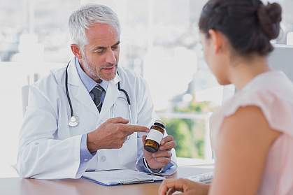 Doctor explaining a bottle of pills to a patient