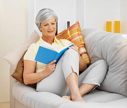 Mature woman on a sofa reading a book