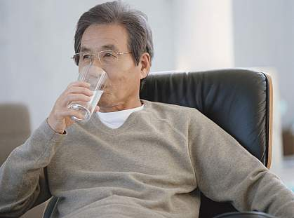 Senior man in an armchair drinking a glass of water