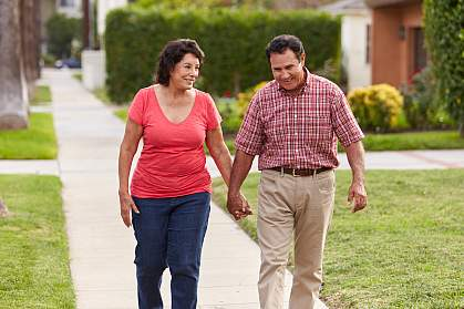 Senior Hispanic couple walking and holding hands on a sidewalk
