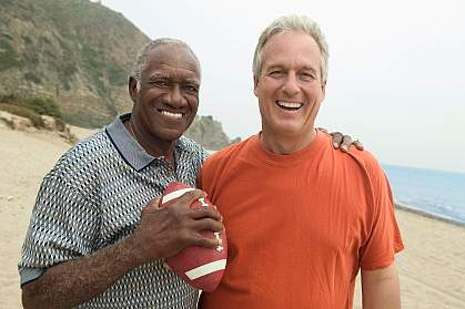Older men, one black and one white, with a football on the beach