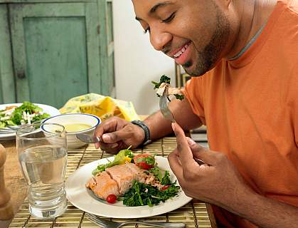 Man happily eating a salmon salad
