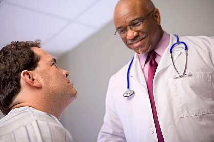 Smiling doctor talking with man in a hospital room.