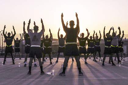 Soldiers stretch during sunrise before an early morning run