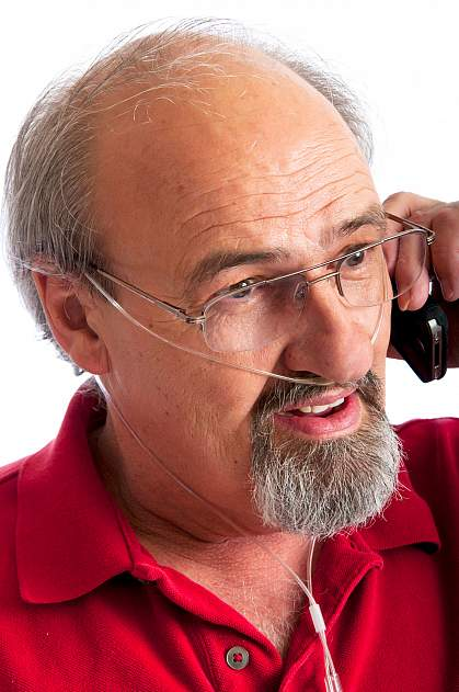 Man talking on the phone while receiving oxygen through a thin nasal tube.