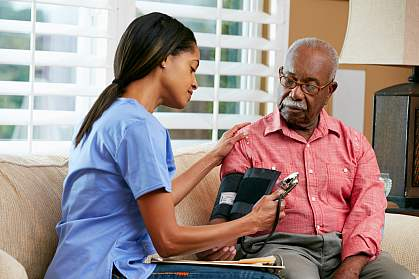 Nurse taking senior man's blood pressure.