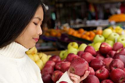 Young woman at store looking at apples