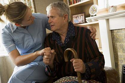 Volunteer visiting senior man with a cane
