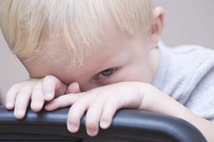 Blonde toddler peeking over a chair