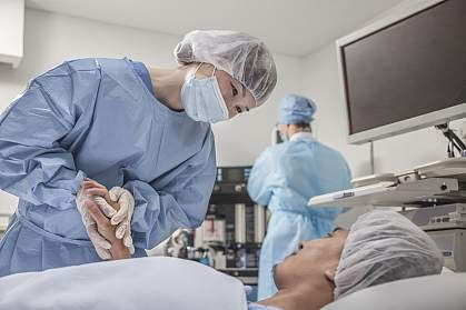 Surgeon holding a patient's hands as they prepare for surgery.