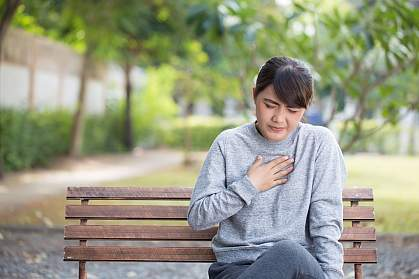 Woman on park bench with heartburn