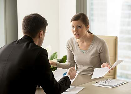 Stressed woman arguing with colleague at work