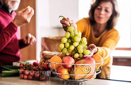 Woman choosing grapes from a basket of fruit