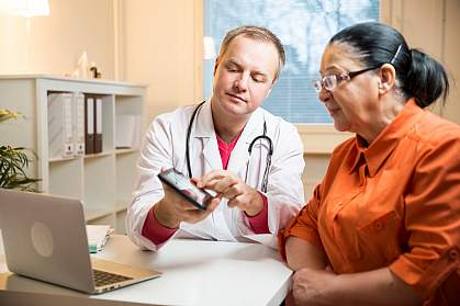 Doctor showing woman something on a tablet.