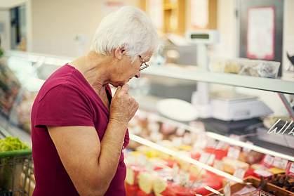 Woman examining cheeses at a market