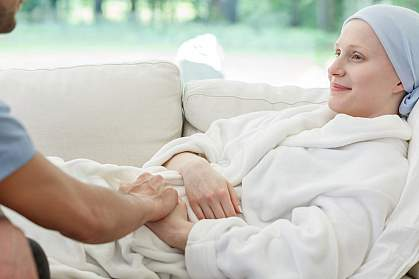 Male nurse supporting a woman battling cancer holding her hand