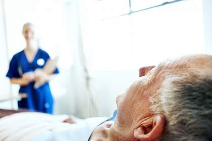 Elderly man in hospital bed with a blurred image of a nurse in the background