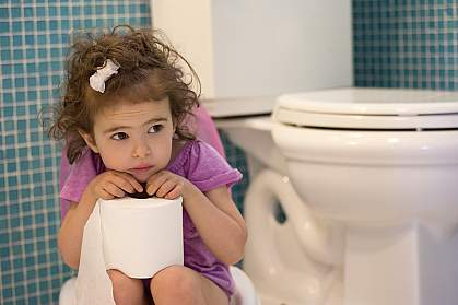 Young girl on children's toilet.