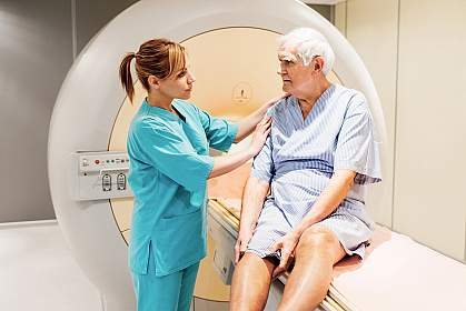 Female nurse preparing a mature patient for an MRI Scan.