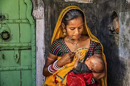Indian woman feeding her newborn baby