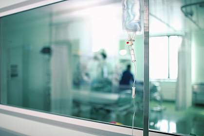 Blurred photo of a hospital room through a corridor window
