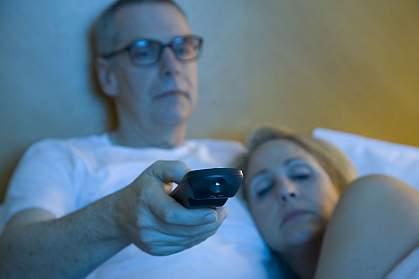 Sleepy couple watching TV in bed