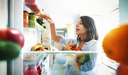 Woman picking fruits and veggies from the fridge