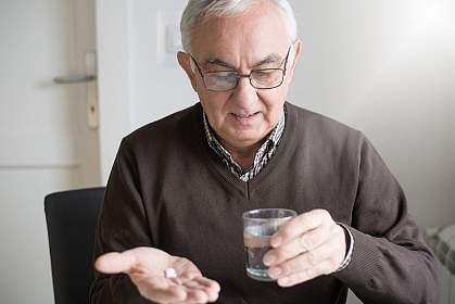 Elderly man looking at medicine and glass of water in his hands