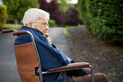 Senior man man sitting in a wheelchair outside.