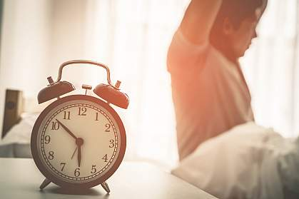 Man stretching out after waking up with alarm clock showing six 'o clock.