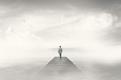 Dream-like photo of man reaching the end of a boardwalk in heavy fog