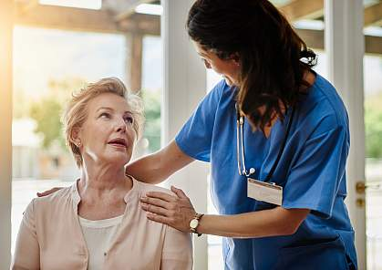 Nurse smiling as she talks to a woman