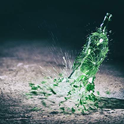 Green wine bottle hitting the floor and breaking