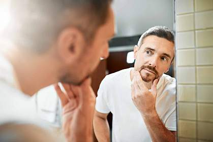 Mature man looking in bathroom mirror at the gray hair in his beard