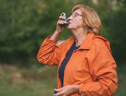 Woman outdoors using an inhaler