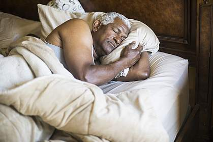 Senior African American man asleep in bed