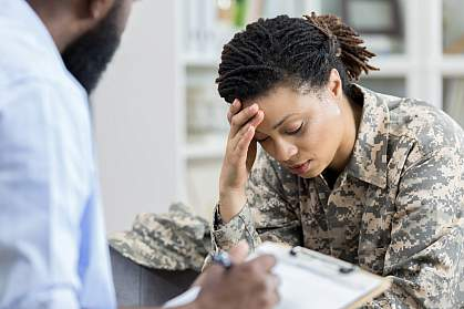 Female military veteran holding her head in an appointment with a health professional