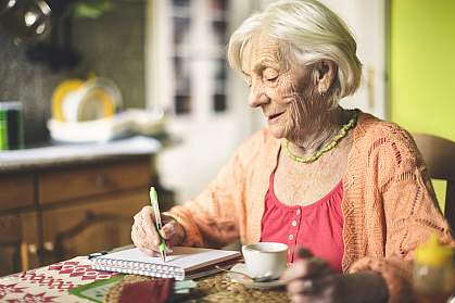 Senior woman in the kitchen writing in a notebook
