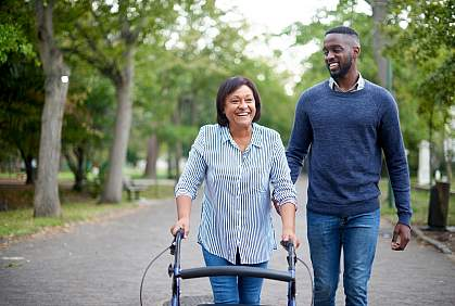 Mature woman using a walker while a young man assists her in the park