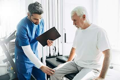 Health professional examining senior man's knee.