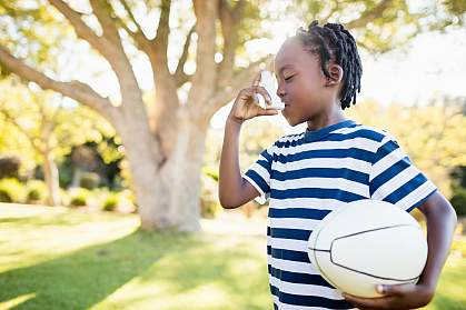 Young child using an inhaler and holding a ball