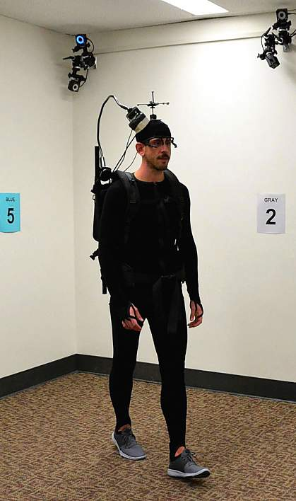 Man walking around room in backpack and headset