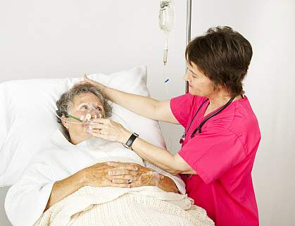 Hospital nurse helping senior woman breath through an oxygen mask