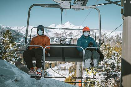 Two skiers with face masks on each side of a chair lift